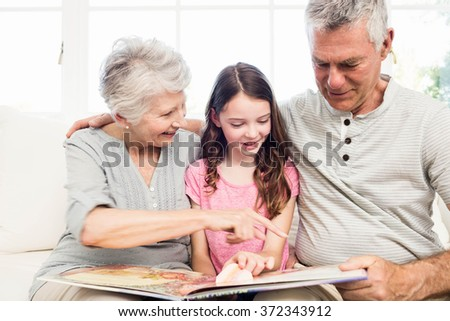 Happy grandparents with granddaughter reading a book on the sofa - stock photo