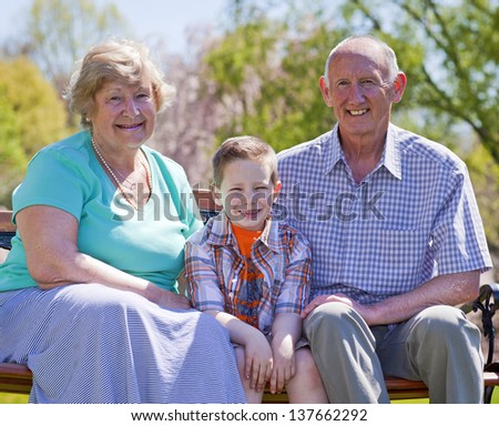 Happy grandparents with their grandson sitting outside