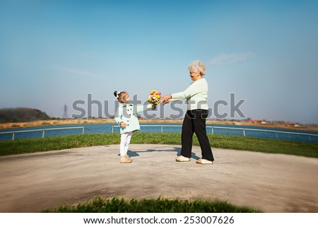 happy grandson giving flowers to grandmother outdoors - stock photo