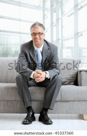 Happy gray haired businessman sitting on couch in office lobby, looking at camera, smiling.