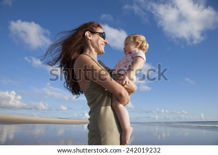 happy green dress woman with sunglasses and one year blonde baby in her arms at beach Conil Cadiz Spain - stock photo