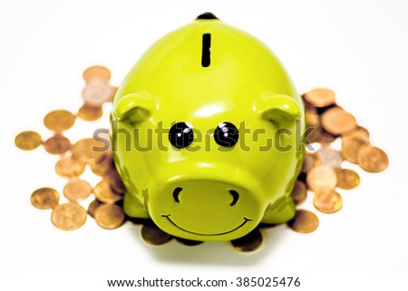 Happy Green Piggy Bank on Lots of Coins - stock photo