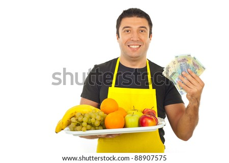 Happy greengrocer holding money and fresh fruits isolated on white background - stock photo