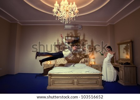 Happy groom flying on bed to his sweetheart in a stylish bed - stock photo