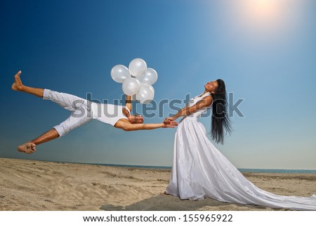 Happy groom flying to his sweetheart on the beach  - stock photo