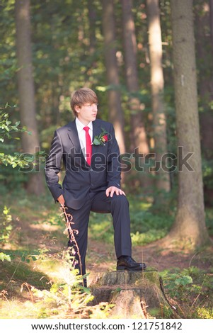 happy groom posing in the summer forest