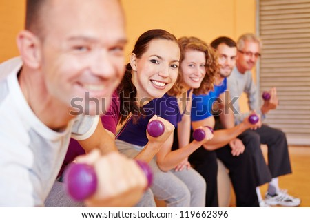 Happy group lifting dumbbells in a fitness center gym - stock photo