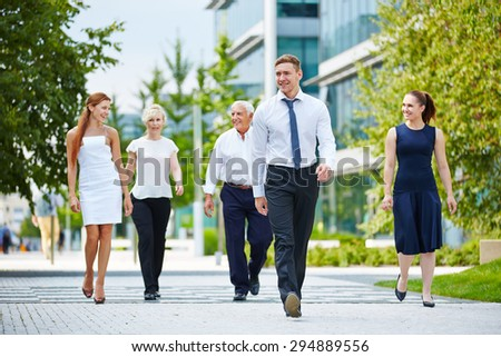 Happy group of business people walking in front of the office - stock photo