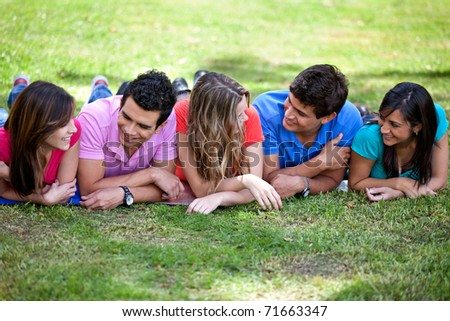 Happy group of casual friends lying outdoors - stock photo