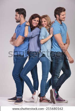 happy group of casual people men looking to sides and women smiling to each other on grey background - stock photo