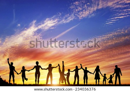 Happy group of diverse people, friends, family, team standing together holding hands and celebrating success. Sunset sky - stock photo