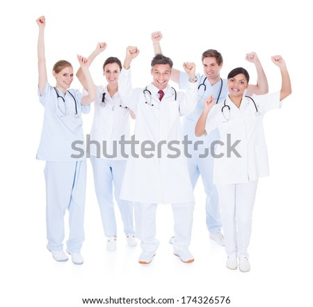 Happy Group Of Doctors Raising Hand Over White Background - stock photo