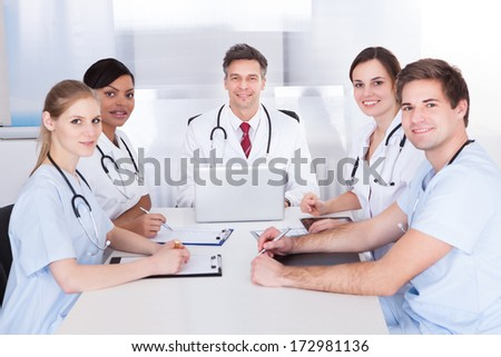 Happy Group Of Doctors Sitting In Meeting With Clipboard And Laptop - stock photo