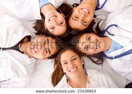 happy group of doctors smiling with their heads together isolated over a White background