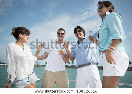 Happy group of friends drinking champagne on a yacht - stock photo