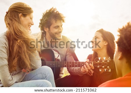 Happy group of friends enjoying the summer outdoor playing guitar and singing together - stock photo