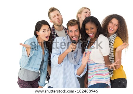 Happy group of friends having fun doing karaoke on white background - stock photo