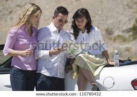 Happy group of friends looking at map - stock photo