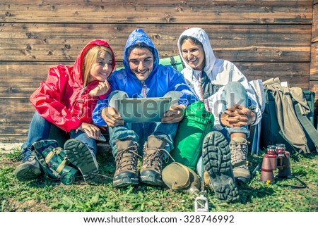 Happy group of friends photographing themselves  - Hikers on excursion in the nature having fun and looking at tablet outside a wooden bungalow in a rainy day