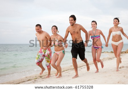 Happy group of friends running at the beach