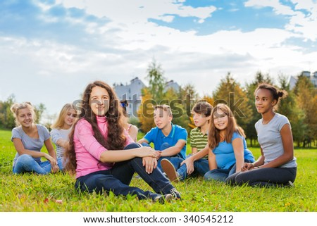 Happy group of friends sit together on meadow