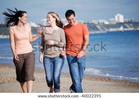 Happy group of friends walking down the beach - stock photo
