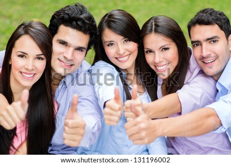 Happy group of friends with thumbs up outdoors - stock photo