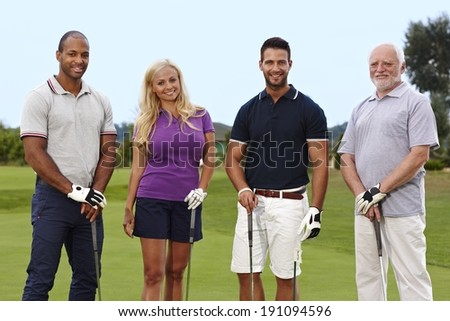 Happy group of golfers standing on the green, holding golf club. - stock photo