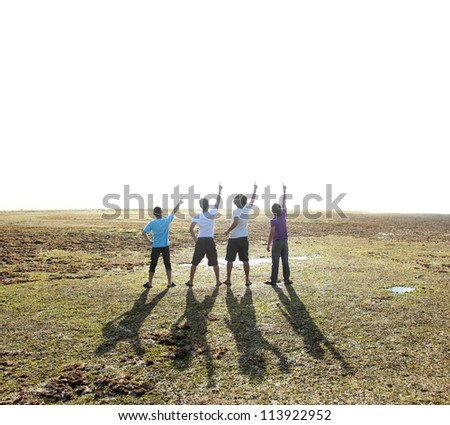 happy group of man pointing up on beach - stock photo