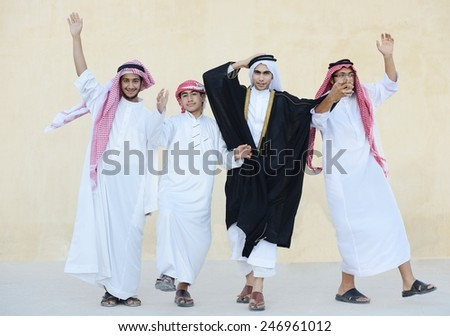 Happy group of Middle eastern Gulf boys dancing and celebrating party - stock photo