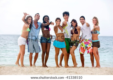 Happy group of people at the beach with thumbs up - stock photo