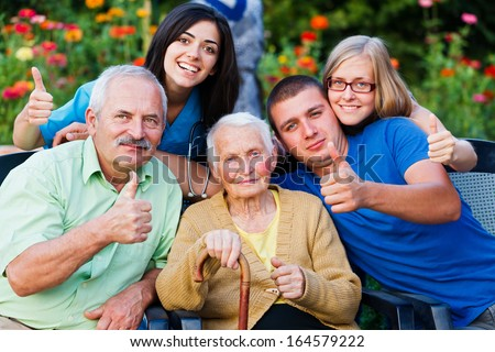 Happy group of people - family and doctor - showing thumbsup for the high quality services in the residential home. - stock photo