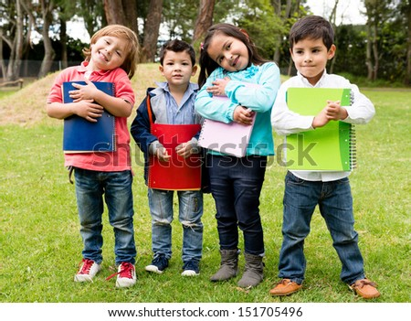 Happy group of school kids holding notebooks outdoors  - stock photo