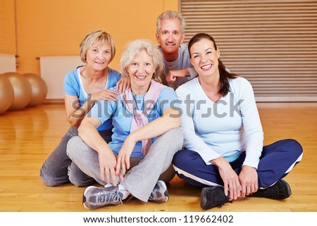 Happy group of senior citizens sitting in a fitness center gym - stock photo