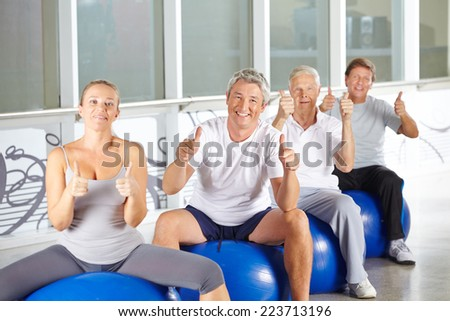 Happy group of senior people in fitness center holding thumbs up - stock photo