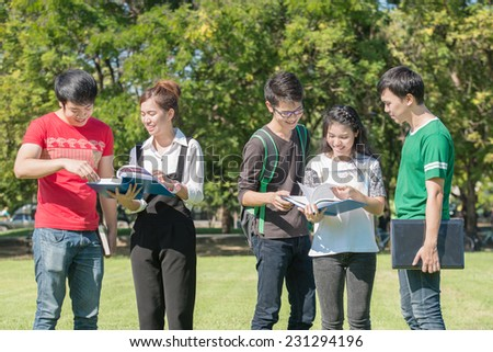 Happy group of students at the park - stock photo