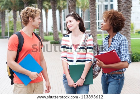 Happy group of students holding notebooks outdoors - stock photo
