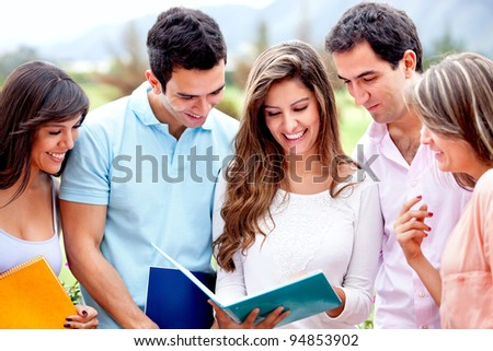 Happy group of students looking at a notebooks outdoors - stock photo