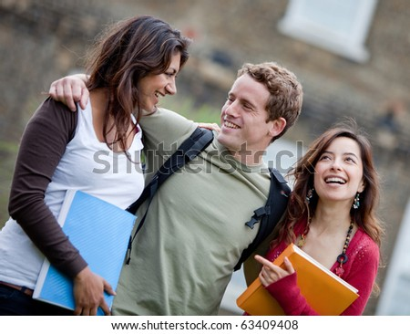 Happy group of students smiling outdoors with notebooks - stock photo