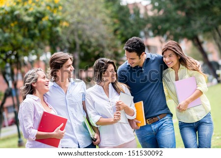 Happy group of students walking at the park  - stock photo