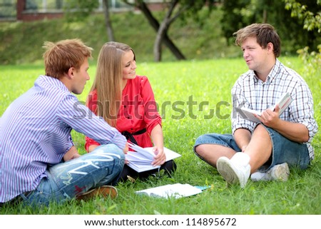 Happy group of students with a notebook smiling outdoors - stock photo