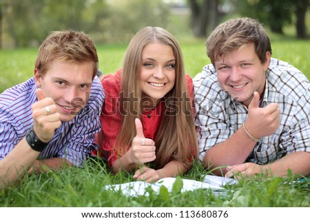Happy group of students with thumbs up - outdoors - stock photo