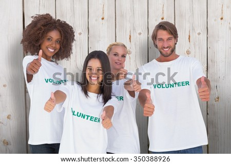 Happy group of volunteers giving thumbs up against wooden background