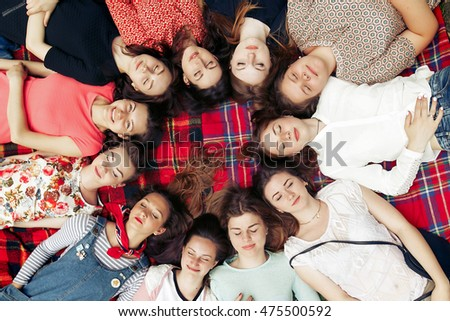 happy group of women faces in circle posing and smiling on picnic top view, lying on blanket, calm and joyful moments celebration in summer park