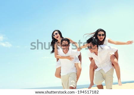 Happy group of young friend doing piggyback together at the beach in summer day - stock photo
