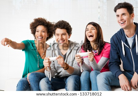 Happy Group Of Young Friends Playing Video Games At Home - stock photo