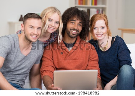 Happy group of young multiethnic friends relaxing together gathered around a laptop computer held by an African American man in the living room of a house smiling at the camera - stock photo