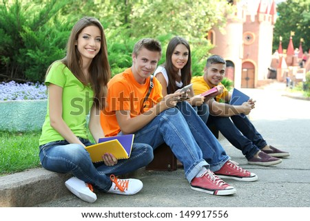 Happy group of young students sitting in park - stock photo