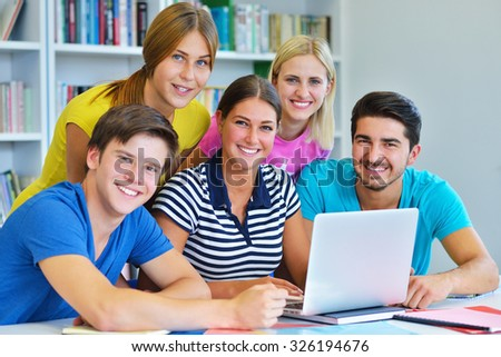 Happy Group Of Young Students Studying Together In Library - stock photo