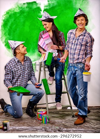 Happy group people paint wall on stairs at home. - stock photo